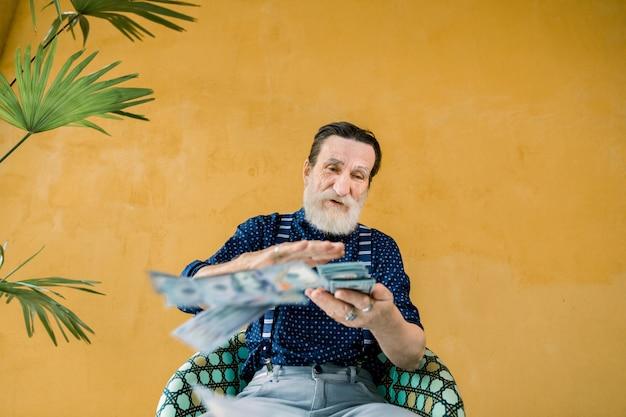 Homem atraente com barba bem cuidada cinza relaxando na cadeira em frente a parede amarela com palmeira e espalhando muitas notas de cem dólares