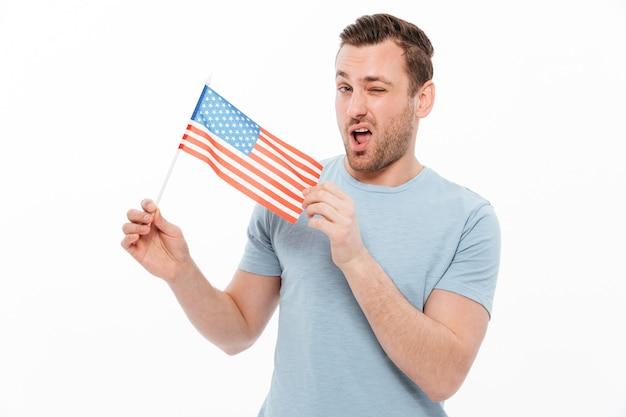 Homem atraente com cerdas demonstrando positivamente a pequena bandeira americana e piscando