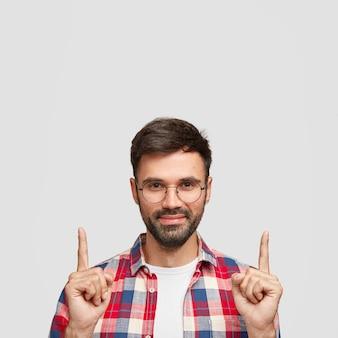 Homem atraente com cerdas escuras, usa camisa casual, indica com o dedo indicador para cima