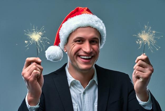 Homem atraente com estrelinhas celebra o ano novo. estúdio atirando em um fundo cinza.