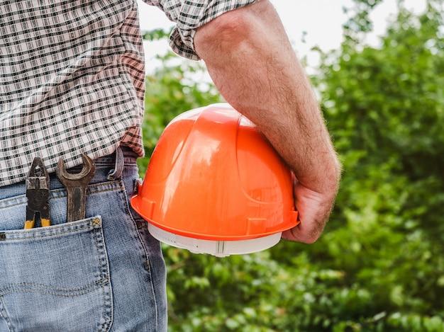 Homem atraente com ferramentas, segurando um capacete de segurança. vista de trás, close-up. conceito de trabalho e emprego