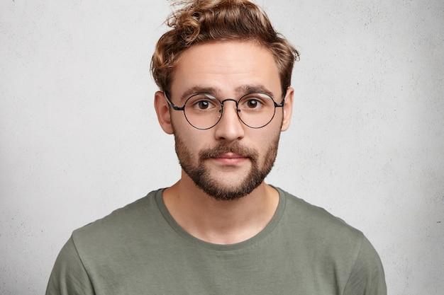 Homem atraente com olhos escuros, barba e penteado moderno, usa roupas casuais e óculos