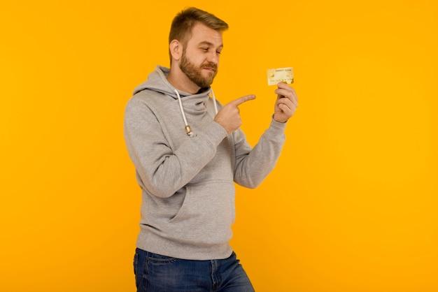 Homem atraente com um moletom cinza aponta um dedo para o cartão de crédito que está segurando em um fundo amarelo