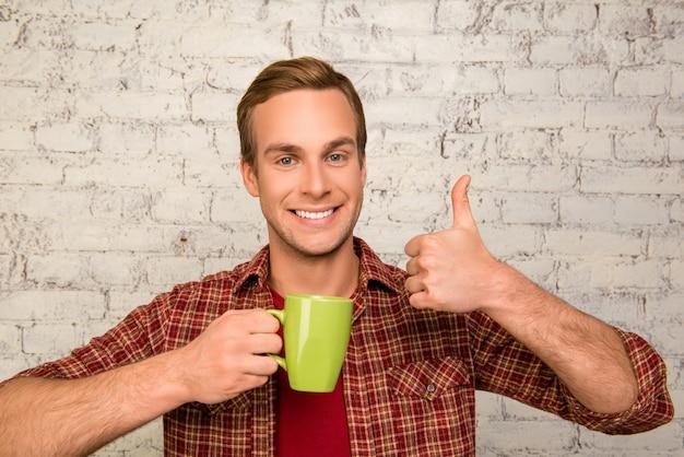 Homem atraente com uma xícara de chá aparecendo com o polegar