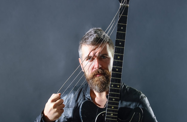 Homem atraente com violão, guitarrista da moda e guitarrista clássico do passatempo musical