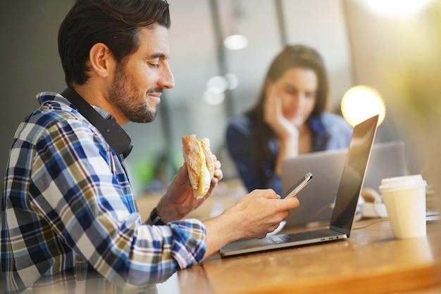 Homem atraente comer sanduíche enquanto trabalhava no espaço de trabalho de co