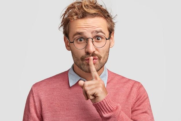 Homem atraente conta um segredo para um amigo próximo, espera lealdade e silêncio, faz gestos de silêncio, usa roupa casual