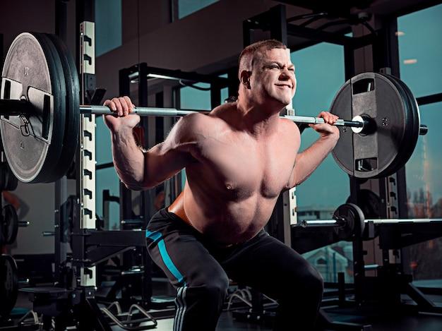 Homem atraente dá certo com halteres no ginásio