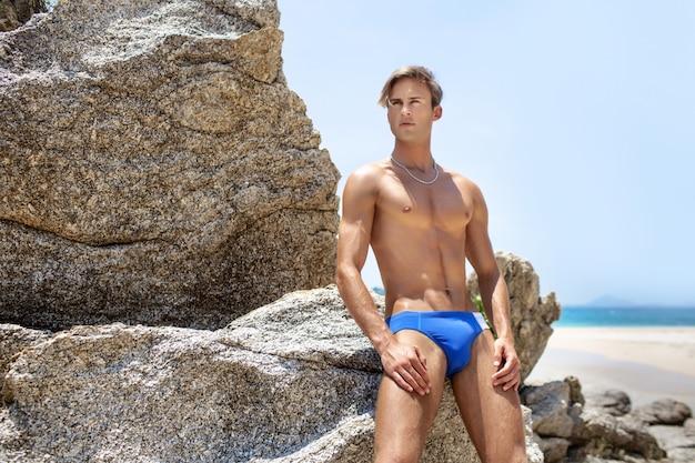 Homem atraente de aparência europeia posando perto de um penhasco em uma praia tropical.