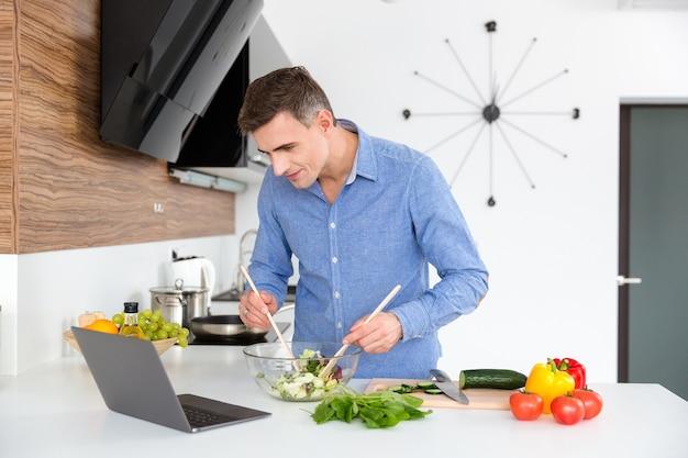 Homem atraente de camisa azul olhando para a tela do laptop e cozinhando na cozinha