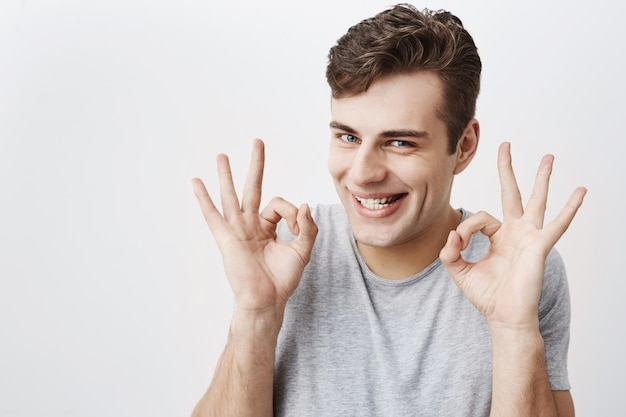 Homem atraente de olhos azuis, sorrindo com alegria, mostrando sinal de ok com as duas mãos, contente após o encontro com sua namorada isolada. expressões faciais humanas e emoções