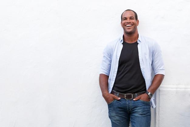 Homem atraente de pé e rindo no fundo branco