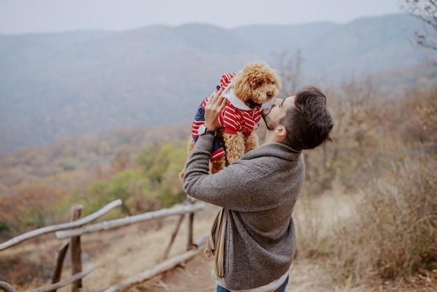 Homem atraente de raça mista, segurando seu cão amoroso em pé na natureza no outono.