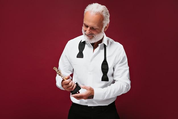 Homem atraente de terno segurando a estatueta do oscar