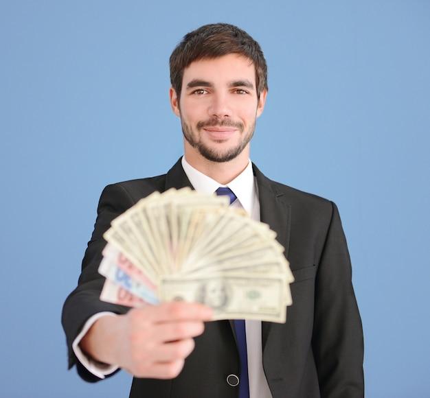 Homem atraente de terno segurando um leque de notas de dólar e euro no azul