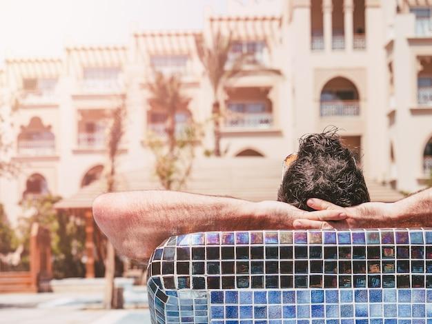 Homem atraente deitado em uma espreguiçadeira no fundo da piscina