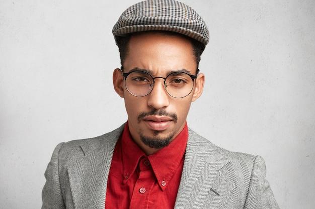 Homem atraente e confiante com rosto oval, usa óculos redondos, vestido formalmente,