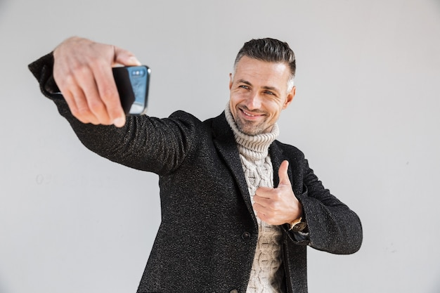 Homem atraente e feliz vestindo um casaco de pé isolado na parede cinza, tirando uma selfie e dando sinal de positivo