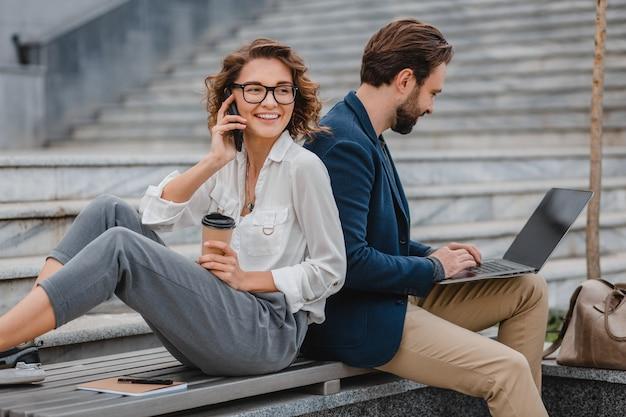 Homem atraente e mulher sentada na escada no centro urbano da cidade