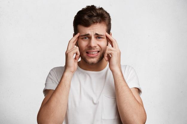 Homem atraente e nervoso em desespero tem expressão desagradável, mantém os dedos nas têmporas, veste-se casualmente, cerra os dentes,