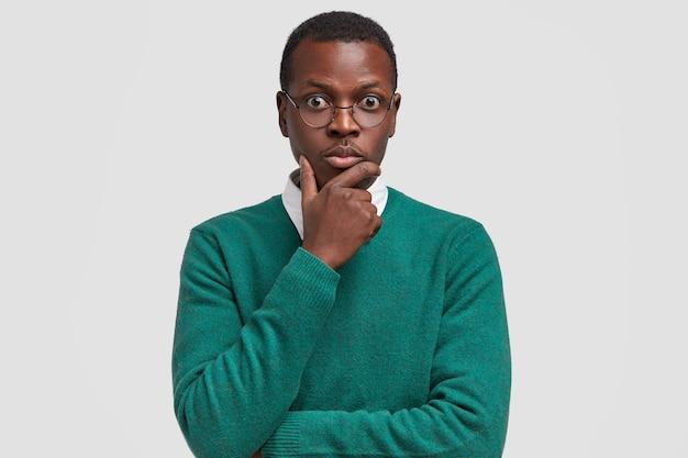 Homem atraente e surpreso sério segurando o queixo, olhando para a câmera com os olhos arregalados, usa um suéter casual e escuta com expressão chocada