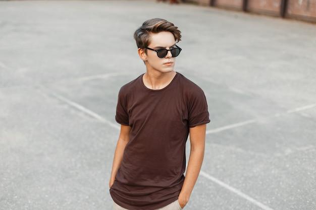 Homem atraente elegante jovem hippie em uma camiseta marrom da moda com um penteado estiloso em óculos de sol da moda na quadra de basquete