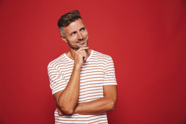 Homem atraente em camiseta listrada sorrindo e tocando o queixo isolado no vermelho