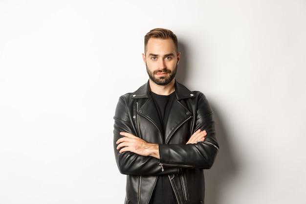 Homem atraente em jaqueta de couro sorrindo, parecendo confiante com as mãos cruzadas no peito