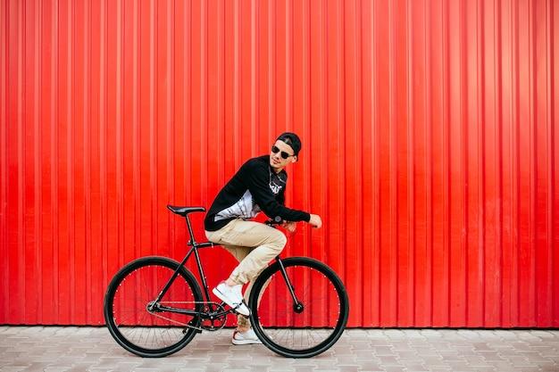 Homem atraente em óculos de sol, sentado na bicicleta profissional, montando, olhando para trás