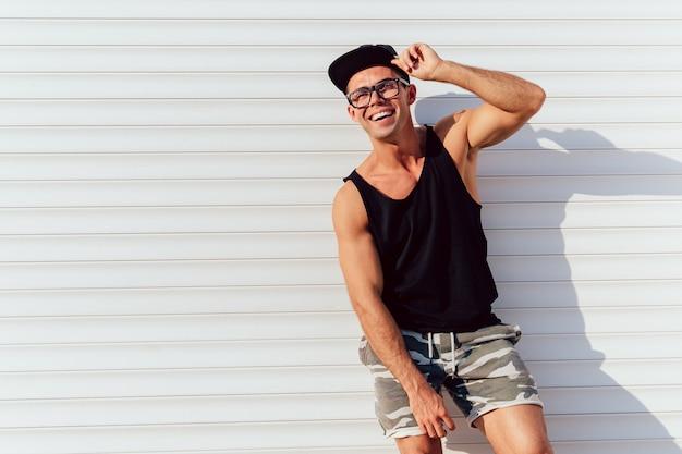 Homem atraente engraçado em óculos posando perto da parede urbana, vestindo camiseta preta