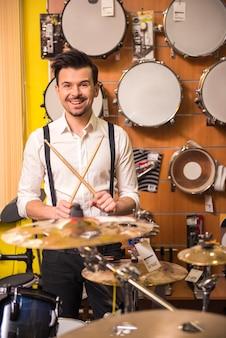 Homem atraente está tocando bateria na loja de música.