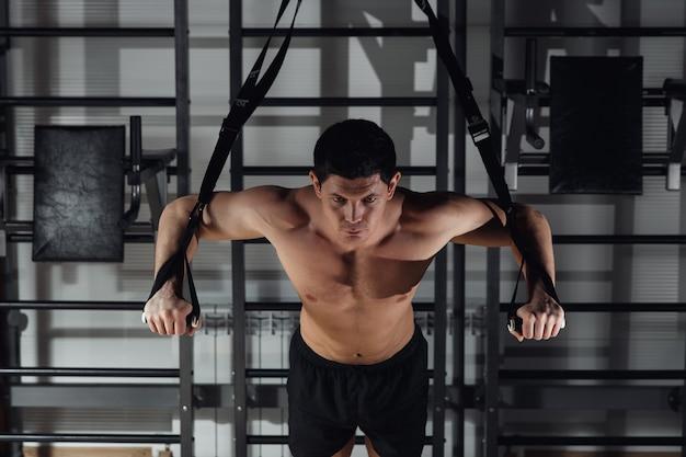 Homem atraente faz crossfit push-ups com alças trx fitness no estúdio do ginásio.