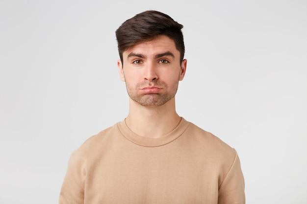 Homem atraente fofo com barba por fazer parece triste e ofendido