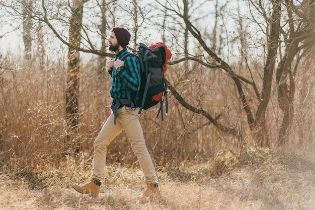 Homem atraente hippie viajando com mochila na floresta de outono, usando chapéu e camisa quadriculada