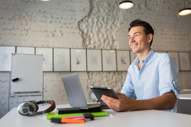 Homem atraente hipster usando dispositivos, trabalhando em um laptop e tablet