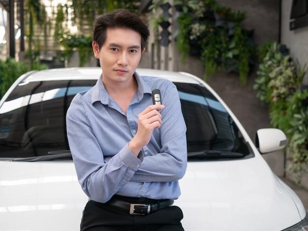 Homem atraente jovem asiático em pé perto de um carro na concessionária e mostrando as chaves do carro.