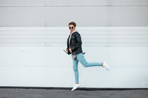 Homem atraente jovem hippie de óculos escuros em uma jaqueta de couro preta da moda em um moletom rosa claro em jeans azul com tênis branco mostra o salto perto da parede branca. cara americano fofo