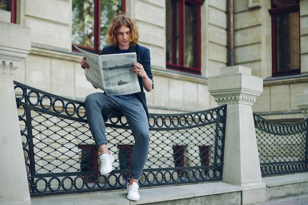 Homem atraente lendo jornal perto de edifício de estilo antigo