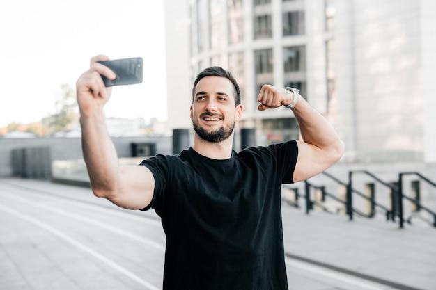 Homem atraente mostra o bíceps e tira uma selfie. conceito de mídia social. atleta masculino em t-shirt preta mostra aos amigos em um videocassete seu corpo apto. treino matinal. conceito de esporte urbano.