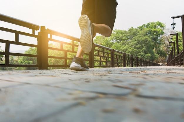 Homem atraente que corre rápido ao longo da ponte em um parque