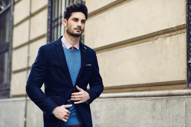 Homem atraente que usa terno elegante britânico na rua. penteado moderno.