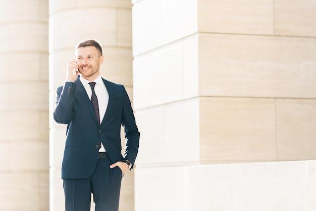 Homem atraente resolve problemas de trabalho com parceiro de negócios durante conversa telefônica