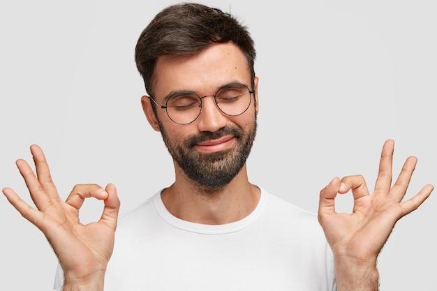 Homem atraente satisfeito com uma espessa barba escura, faz um gesto bom com as duas mãos, mostra sua aprovação