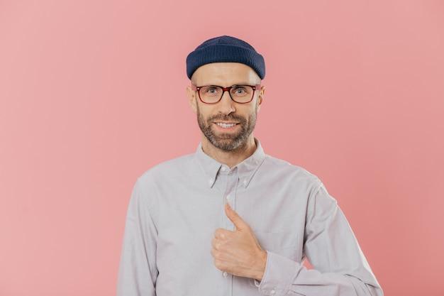Homem atraente satisfeito tem aparência atraente, levanta polegar, concorda com algo, sorri feliz