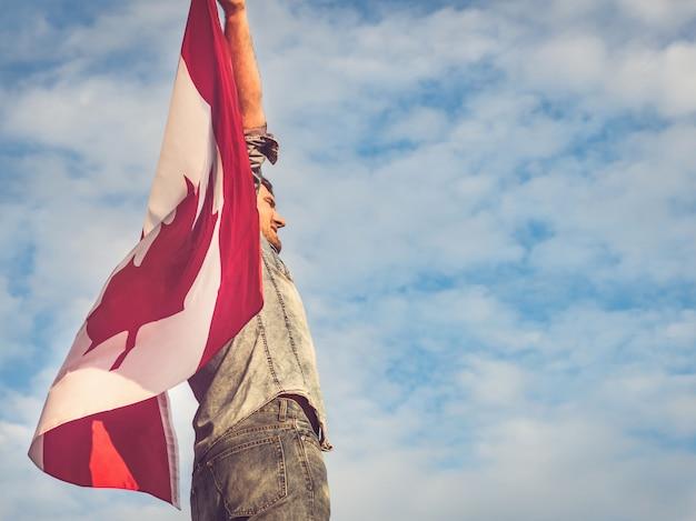 Homem atraente, segurando a bandeira do canadá