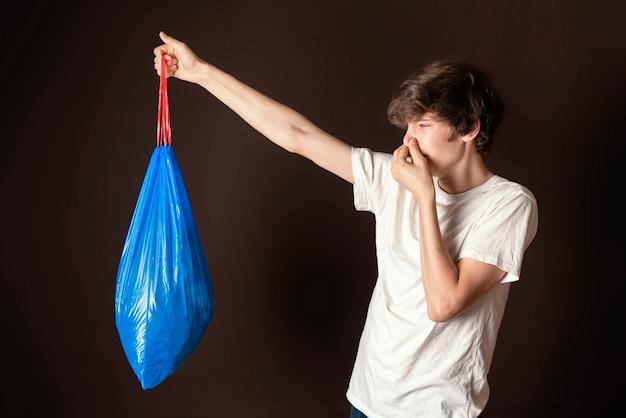 Homem atraente segurar o saco de lixo fedorento isolado. levar para fora os conceitos de lixo