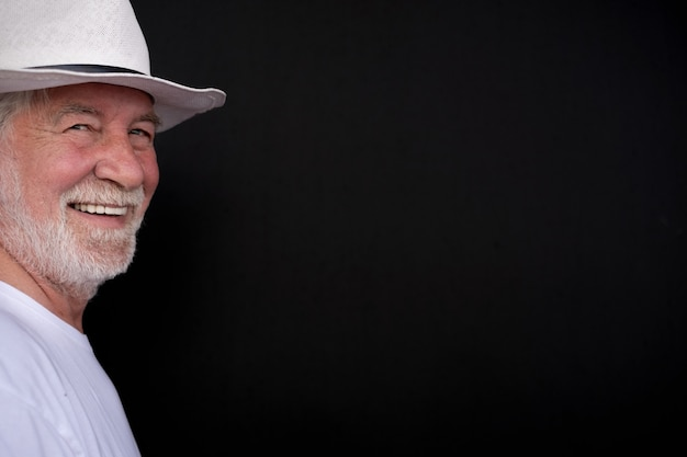 Homem atraente sênior com chapéu branco e camiseta, olhando para a câmera sorrindo. retrato de idoso aposentado de cabelos brancos e barba. fundo preto