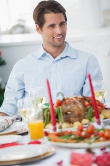 Homem atraente sentado à mesa para o jantar de natal