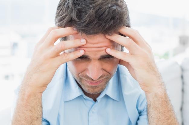 Homem atraente sentado no sofá com dor de cabeça