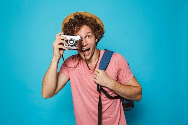 Homem atraente turista com cabelos cacheados, usando mochila e chapéu de palha fotografando na câmera retro